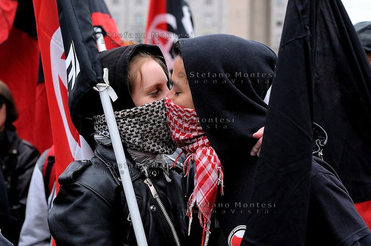 Milan, May 1, 2015 Mayday NoExpo Clashes protesters against police during the demonstration in downtown Milan, to protest against Universal Exposition Milano 2015. Two girls kiss each other before the demonstration