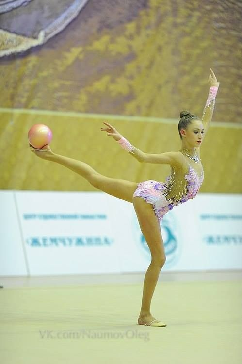 Maria Titova   That has to involve strength, balance, & control of a high level. She is gripping the ball with her foot. And balancing with this weight on her outstretched leg. Rhythmic gymnasts are amazing.