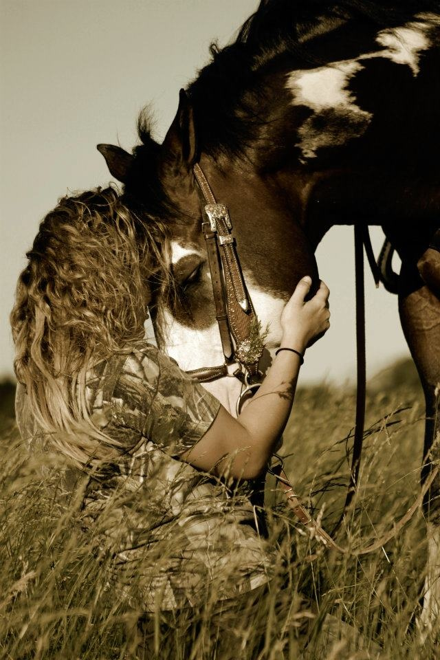 Girl snuggling, hugging and loving on her Horse. Paint colored horse bending down to nuzzle.
