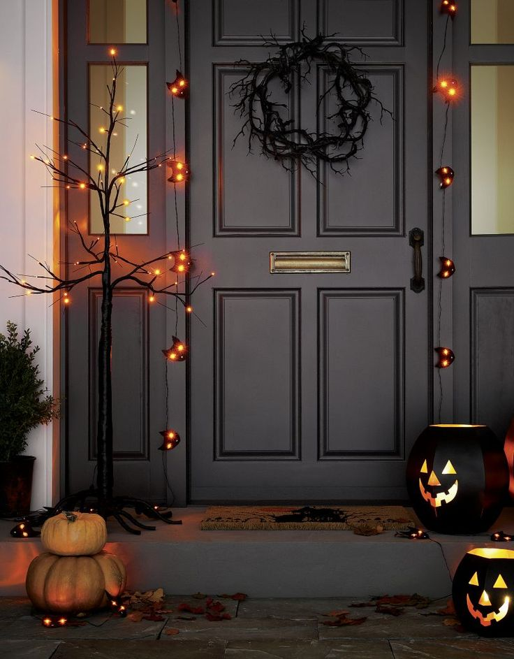 orange led lights add spooky illumination to bare branched black halloween tree decoration that