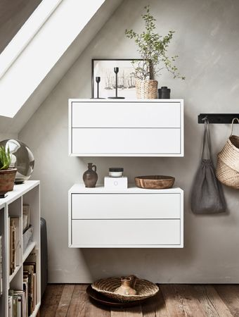 Two white wall cabinets hold small decorative items on top.
