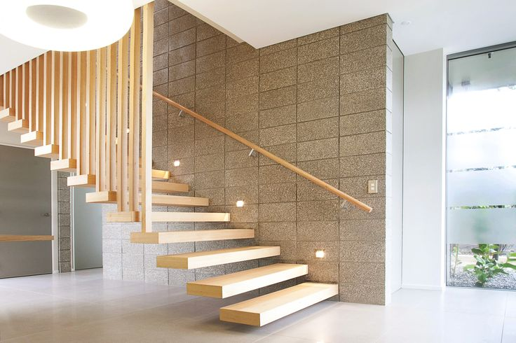 An Australian Oak timber stair which floats off the concrete block, and timber slat balustrade.