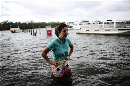 Doreen Mylin, owner of the Magic Manatee Marina, pauses to inspect the damage as the water associated with Tropical Storm Debby rises and floods her business in Homosassa, Florida, June 26, 2012.  [source: ahmadalikarim.wordpress.com]: Storms Debbie, Manat Marina, Manatees Marina, Magic Manatees, Photo, Tropical Storms