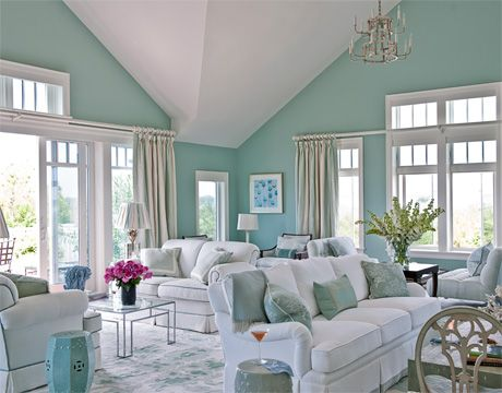 For the coastal location, Coleman painted the living room a soothing watery blue-green, Farrow & Ball's Powder Blue.  Love seats and sofa are covered in Scalamandré's Harper Matelassé. The curtains and lampshades on the vintage mirrored lamps in Bellini Stripe silk by Cowtan & Tout. Milo Baughman chrome-and-glass coffee table from John Rosselli.