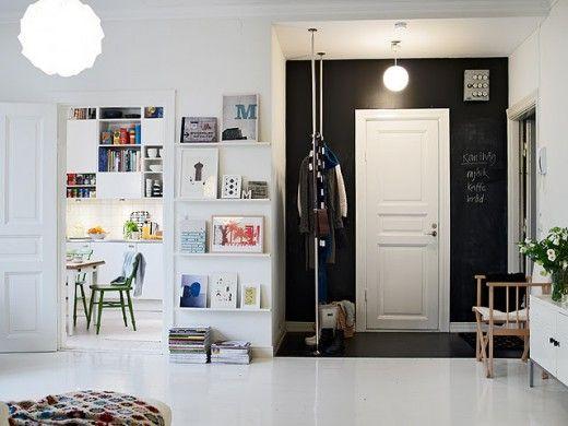 Svartmålad hallvägg och snygg klädförvaring.