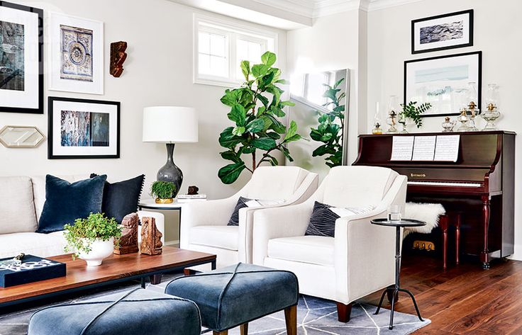 The bright and eclectic living room is a lesson in layering done right. Crisp white walls are warmed by rich hits of blue, lush greenery and a whimsical collection of artwork and antique objets like vintage oil lamps and the piano.