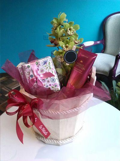 Propuesta sublime: Una propuesta en base de pino con un florero de vidrio mediano, en el cual va una vara de orquídea de minicymbidium, en la manija del balde una cinta roja de La Pétala. Se acompaña con una pequeña caja de chocolates María Elisa de diferentes sabores y una crema Victoria´s Secret. Esto va sobre una wrap de color rojo. Solicítalo ya: Teléfono +571 2159030 o al correo electrónico clientes@lapetala.com Precio $ 120.000