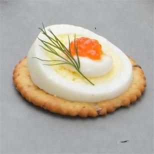 The most beautiful appetizer I like to serve... Caviar Eggs on a Cracker. TIP: I buy black peppered water crackers for the base or make thin, toasted slices of baguette. Slice hard boiled eggs at an angle, add a dollop of sour cream or Greek yogurt, and garnish with salmon caviar. Don't like caviar? Use pimiento, finely chopped carrots and cucumbers, a beautiful olive slice, or a chunk of salmon. It's all good.