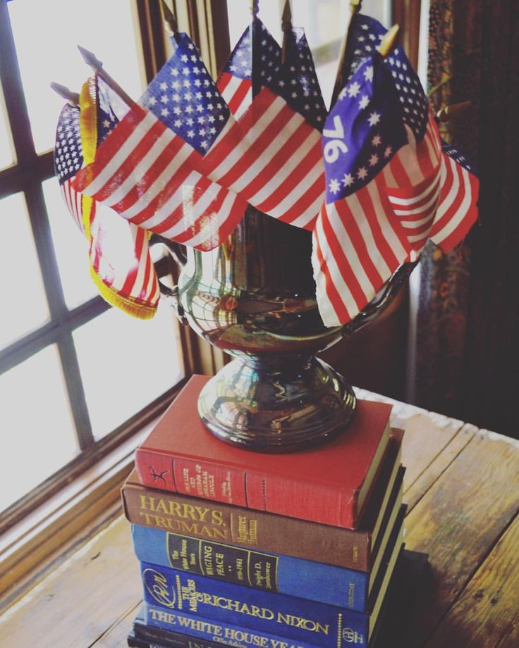 Americana style. Vintage American flags in a vintage silver ice bucket atop vintage books about past U.S Presidents.