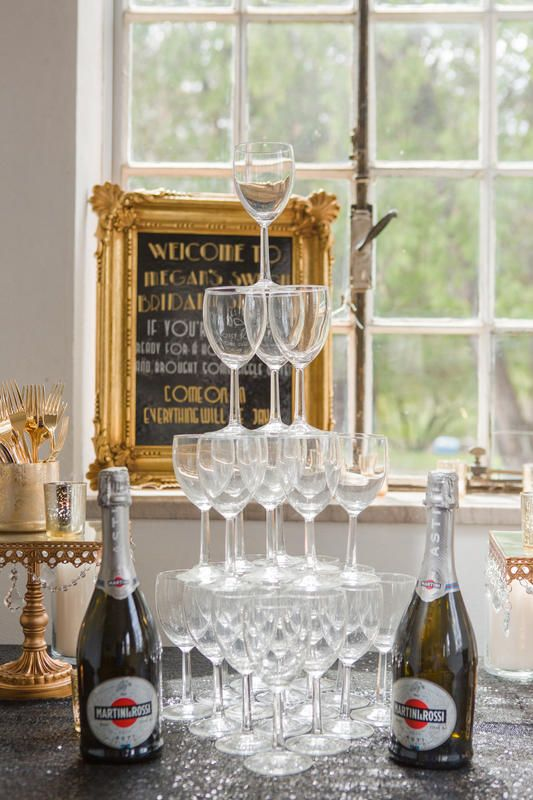 A champagne tower at a bridal shower is always a good idea!   Inspiration for the perfect Great Gatsby-themed bridal shower. Party like it's the 1920s with this roaring 20s, glitzy, glamourous bridal shower inspiration.
