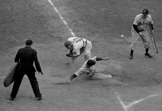 Detroit Tiger second baseman Eddie Mayo slides safely across home plate in the eighth inning of the final World Series game here on Oct. 10, 1945 at Chicago, Illinois. As Chicago Cubs catcher Mickey Livingston (11) bends to trap the outfield throw, which bounces in back of the plate toward Roy Cullenbine, right, next batter. The Tigers won the game 9-3 and the 1945 World Series Championship.