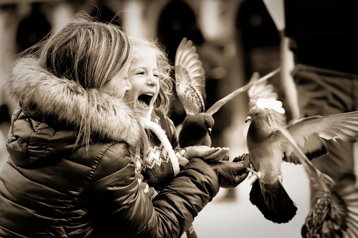 Pigeons, girl, mum, all four of them are happy. Venice, Saint Mark square. #Saint Mark #Venice #black and white #child #feed #girl #happy #italy #lucky #pigeon #sepia #square #venezia
