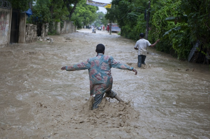 Residents wade through a flooded street caused by heavy rains from Hurricane Sandy in Port-au-Prince, Haiti