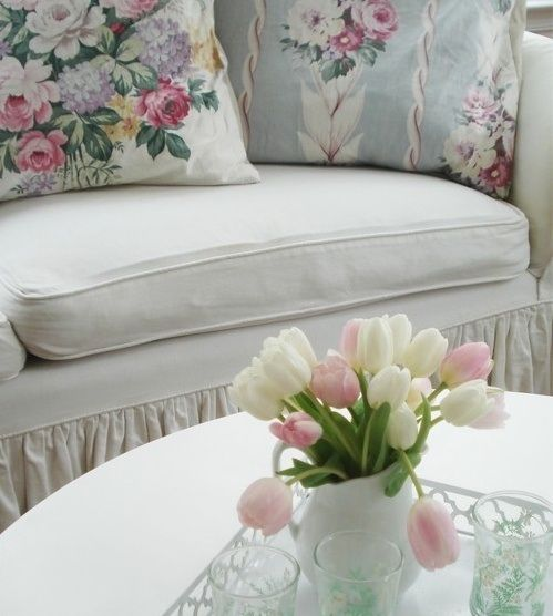 Love the floral additions to the decor.  Like the skirted sofa. This section, that we see of the space, is charming.