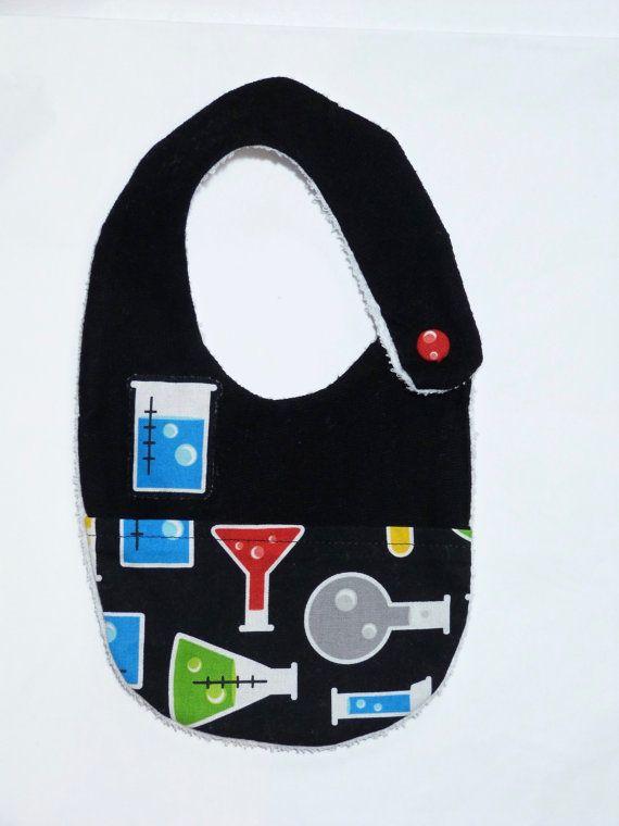 Original Babero hecho a mano. Está compuesto por una capa te tela de rizo impermeable blanca, una capa superior de forro negro, y un bolsillo. Se
