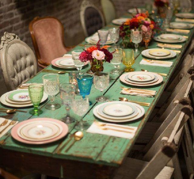 Mesa de comedor estilo rústico de madera pintada verde. Menaje de distintos colores y sillas diferentes.