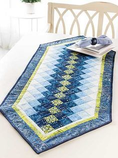 """So fun to make! Pick a half yard of your favorite fabric and add 4 shades from light to dark of a coordinating color to create this easy-to-piece runner. Can also be made using your favorite 2 1/2"""" strips. Make one to match your kitchen or make several to change out for each holidays. Finished size is 55"""" x 21"""" using 23 (2 1/2"""") strips or 6 fat quarters."""