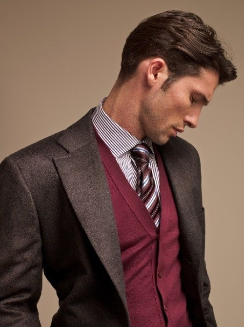 Brown suit jacket, dark red sweater vest, button up dress shirt, with stripped tie on male model