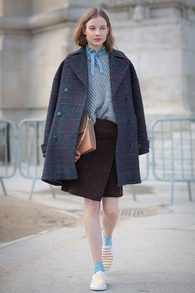 Michelle Meinert    ドイツ出身のモデル、ミシェルはバランス感覚抜群の着こなしで注目を集める存在。この日はデニム地のボウブラウスとグレーのニットを重ね着。水色のソックスとオレンジのボーダー柄スリッポンを合わせるセンスがさすが!   写真2:白いコートを羽織り、上半身にボリュームを集めて。ラフにカットされたデニムパンツの裾に、気負いのなさが漂う。白いパンプスが着こなしをぐ...