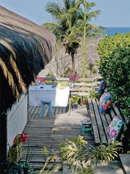 Cabana de praia com 36 m² ganha ares de loft - CasaO bangalô foi cercado de deques feitos de cruzetas (Geraldo Vieira Marcenaria), mantidas sem tratamento. Somente o banco recebeu uma demão de stain. Almofadas coloridas da Orlean.