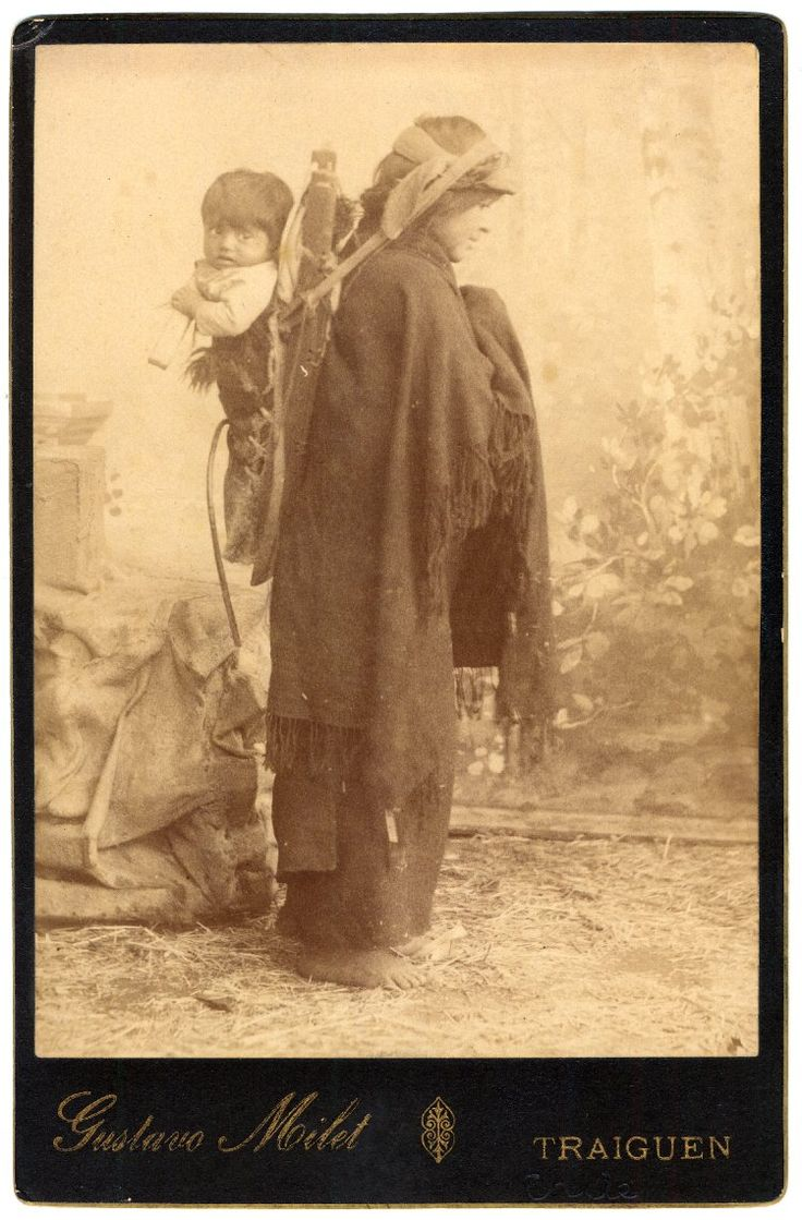 ca 1890- A studio portrait of a Mapuche woman and baby seen standing in profile, posed in front of a painted background of an outdoor scene; the woman wears a trarilonko (hair lace/headgear), quipan ( a square cloth, wrapped around the body), and ikulla (shawl) or manta (blanket); she carries the baby in a baby carrier made of wood and cord on her back; Traiguen, Chile.