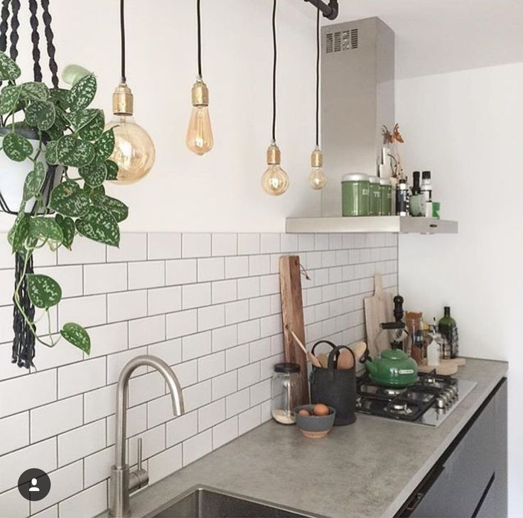 Great kitchen lighting with bare bulbs white metro tiles. Machrime hanging plant holder and stainless steel worktop counter surface Scandi style home