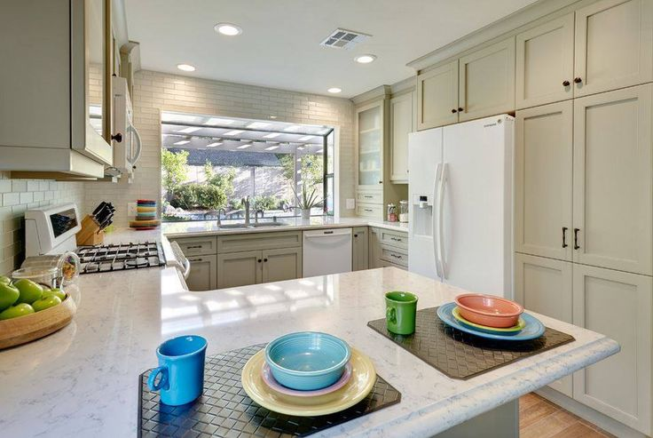 Doing dishes is anything but a chore when a window lets you drift off into the view beyond the kitchen sink. cabinetsanddesigns.net