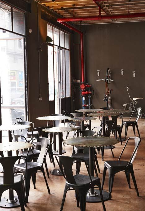 Original cast-iron columns are dotted across the room, while new glass doors open the cafe out to the street