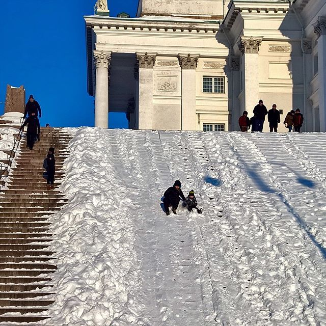 Winter fun at the stairs of Helsinki Cathedral. Sliding down steep snowy stairs - fun for adults and kids too!