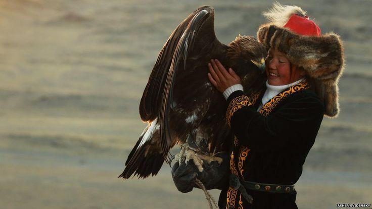 Mongolian eagle hunters: Ashol-Pan cuddling her eagle