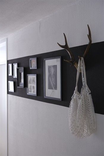 Frames and antler 'hooks' mounted on dark horizontal panel on a light wall