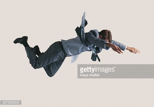 Stock Photo : Businessman hanging in the air, wearing grey suit