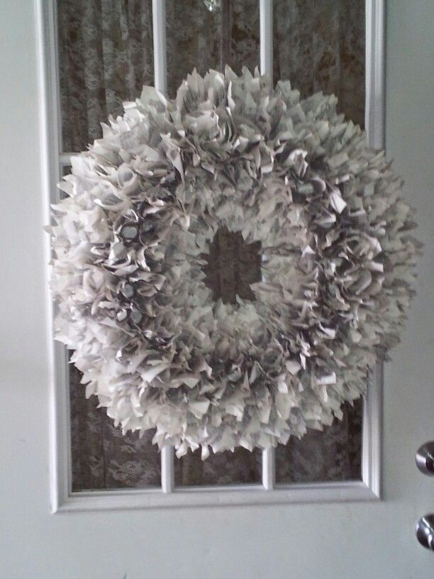 Used $1 pool noodle duct taped (to give form strength and shape and hot glue wouldn't melt foam as much) for wreath form, apx. 400, 5 inch squares cut from old dictionary,  hot glued using mascara tube for shaping tool. Took about an hour just to glue! It was a fun project.