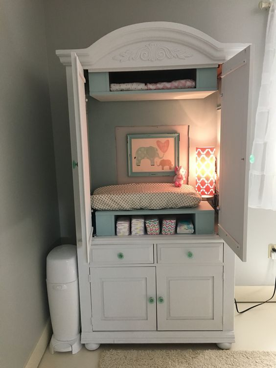 an armoire hides a changing table, storage and some additional light and makes the room look neat