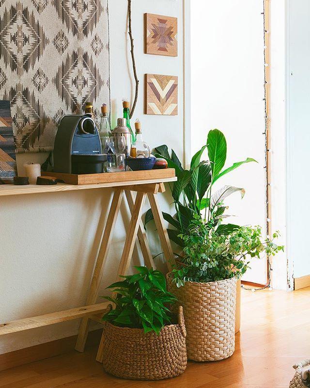 aparador de cavaletes, que é sempre uma boa ideia, cestos de fibra em cachepôs charmosos para as plantas... na parede, as telas de marchetaria   foto: @lflorenzano_fotografia