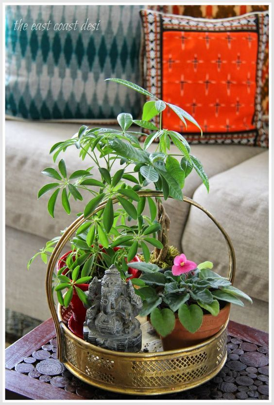 A traditional Indian antique brass puja basket is filled with indoor plants and a stone Ganesha