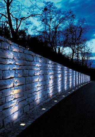 un semplice muro di pietre illuminato suggestivamente con faretti led a luce fredda