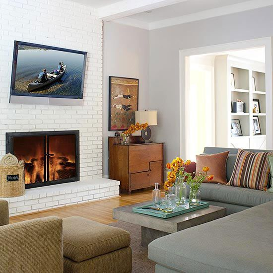 A white brick fireplace gives a clean, sophisticated look to this living room. Light gray walls and the simple, white fireplace contrast the dark furniture and area rug. The plain black doors on the firebox and the sleek TV mounted above stand out against the crisp white bricks, and the elevated hearth adds more dimension to the room. Brick fireplace designs bearing a dark or dated finish can easily be updated with paint. Click the link below to learn how./