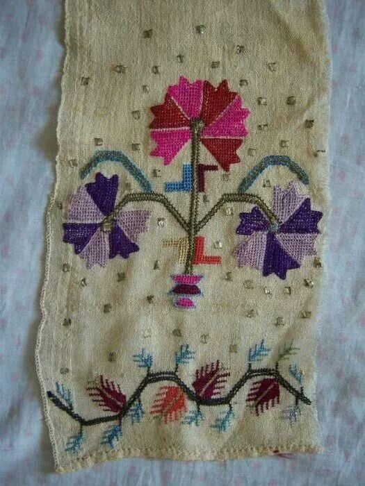 One (adorned) end of an 'uçkur' (sash / waist band).  Early 20th century.  'Two-sided embroidery' (both sides are identical) - silk and metal thread on linen.  Motif: 'Karanfil' (carnation).  'Tel kırma'-technique: geometrical motives obtained by sticking narrow metallic strips (often silver) through the fabric and folding them; this motifs too are identical on both sides of the fabric.
