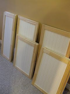 Kitchen Cabinet Makeover - add trim around the edges and paintable bead-board wallpaper to the fronts.