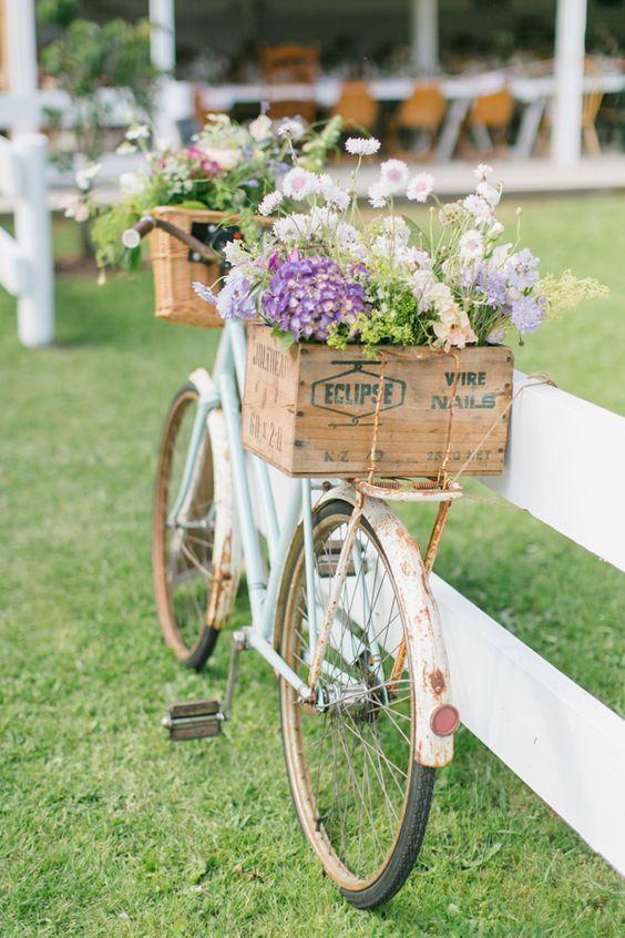 fruit bin filled with flowers on the rusty ol' cruiser bike