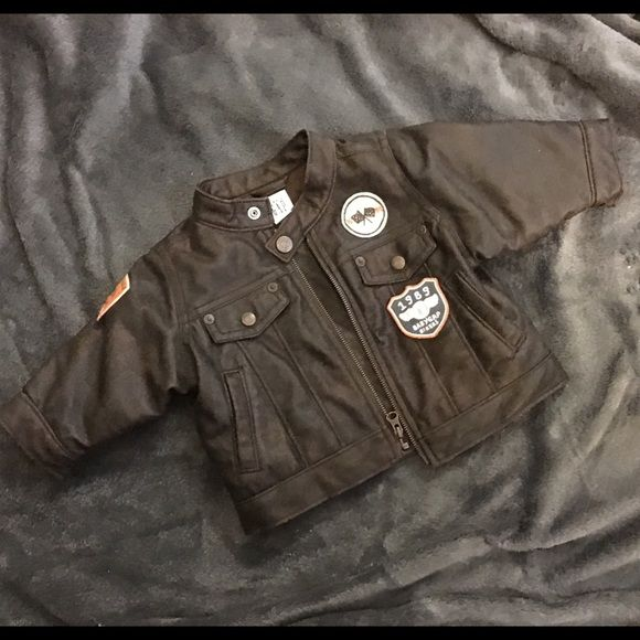 Baby Bomber Jacket from The Gap Faux leather baby bomber jacket. Just like daddy's coat....this has biker patches. A button closure on the thin tab collar. Only worn a couple times. Tag says 0-6 months but runs big. GAP Jackets & Coats