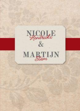 Klassieke trouwkaart met bruin kraftpapier en hele licht grijze bloemen eroverheen. Recycle etiket met jullie namen en donkerrode band.