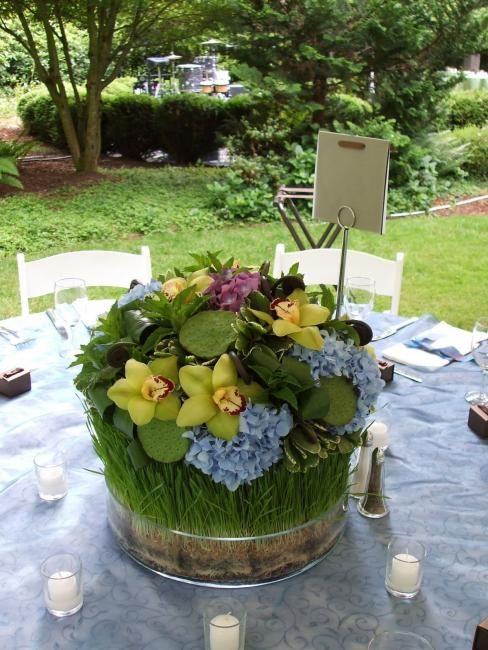 A wheat grass collar wraps these centerpieces containing hydrangea, fresh lotus pods, cymbidium orchids and mint.