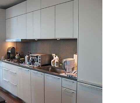 modern elephant gray kitchen cabinetry with stainless steel trim was designed for a residential high