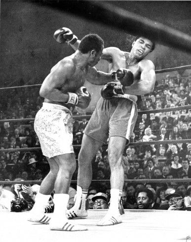 Muhammad Ali takes a hit from Joe Frazier in their 1971 bout.