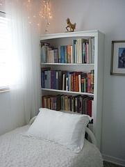 Bookshelf as a headboard. Great space saving idea.