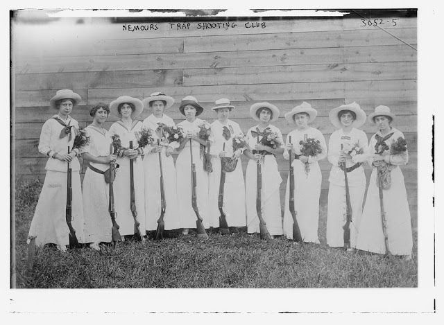 Female members of the Nemours Trap Shooting club holding their riffles and a bouquet of flowers each