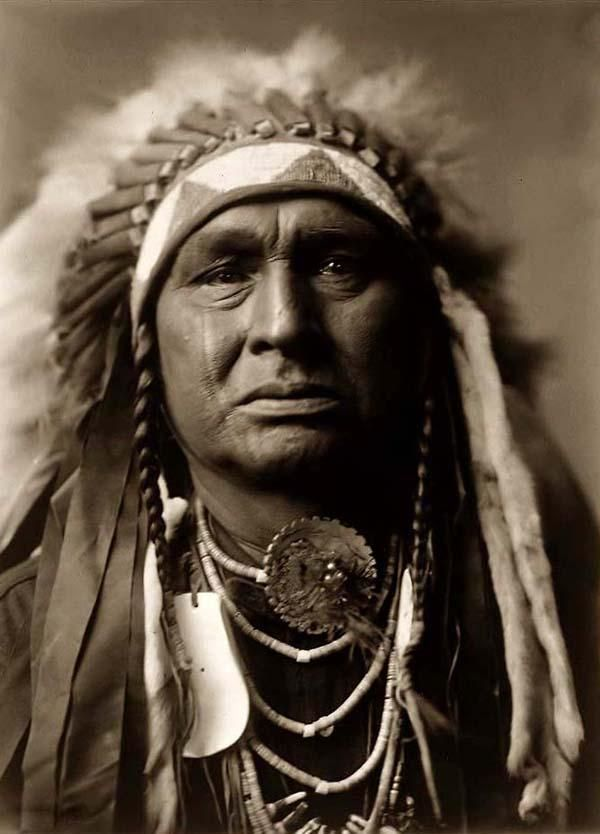 majestic photo of White Man Runs Him, a Crow (Apsaroke) Warrior. It was made in 1908 by Edward S. Curtis.    The illustration shows this Indian wearing a War Bonnet feather, concho shells, and shell beads around his neck.    We have compiled this collection of artwork mainly to serve as a vital educational resource. Contact curator@old-picture.com.    Image ID# F63D0CC7