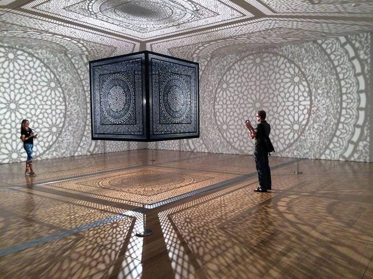 L'artiste pakistanais Anila Quayyum Agha a créé cette oeuvre composée d'un cube de deux mètres de coté en bois finement découpé au laser avec une lumière en son centre qui projette ses motifs sur les murs de la pièce créant l'impression qu'ils sont ornés de décoration.